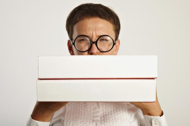 Jonge vrouw student in ronde bril fronsend houdt twee grote mappen met onderwijsplan voor het nieuwe jaar op de universiteit focus op mappen