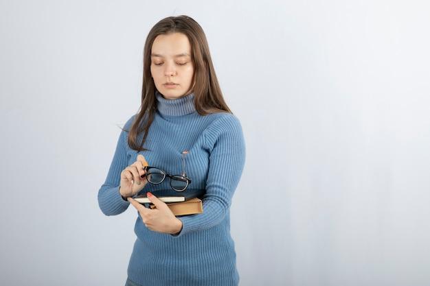 Jonge vrouw student met boeken en glazen.