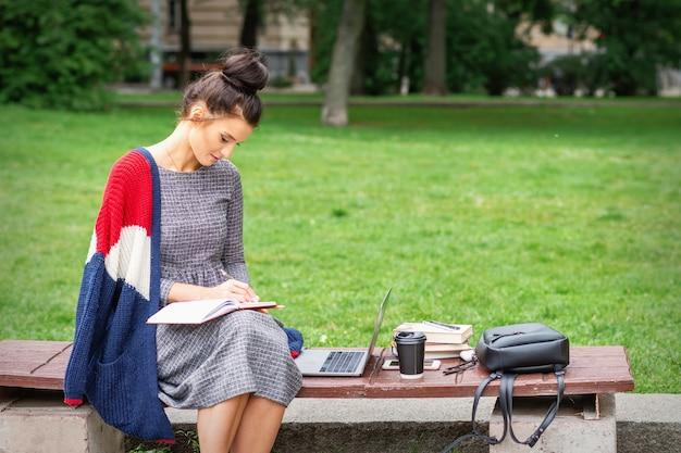 Jonge vrouw student schrijft notities aan dagboek op de bank in het park