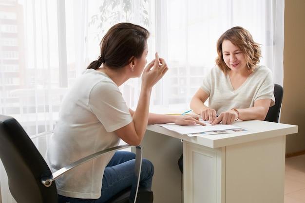 Jonge vrouw studeren met privéleraar aan een tafel, notities maken en lezen
