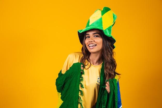Jonge vrouw supporter uit brazilië met vlag en gekleed voor het spel.