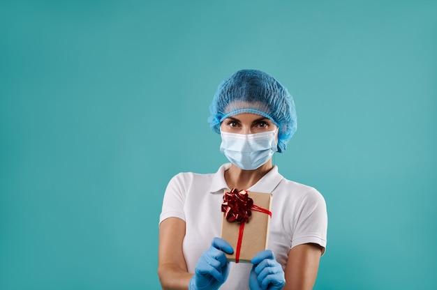 Jonge vrouw tandarts in een hoed en masker houdt een kerstcadeau.