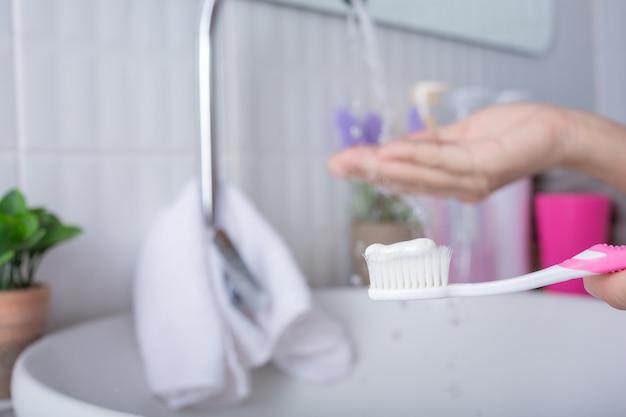Jonge vrouw tanden poetsen.