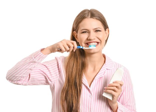 Jonge vrouw tandenpoetsen op wit
