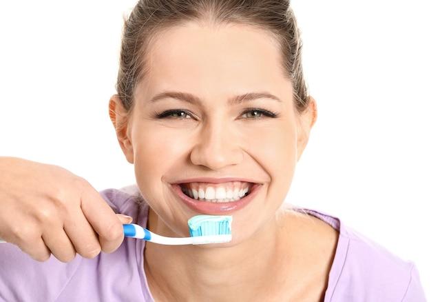 Jonge vrouw tandenpoetsen op witte ruimte