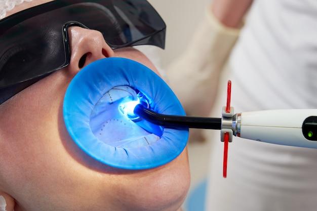 Jonge vrouw tandheelkundige behandeling krijgen bij tandarts kantoor met een tandheelkundige rubberen dam bescherming