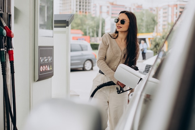Jonge vrouw tankt haar auto