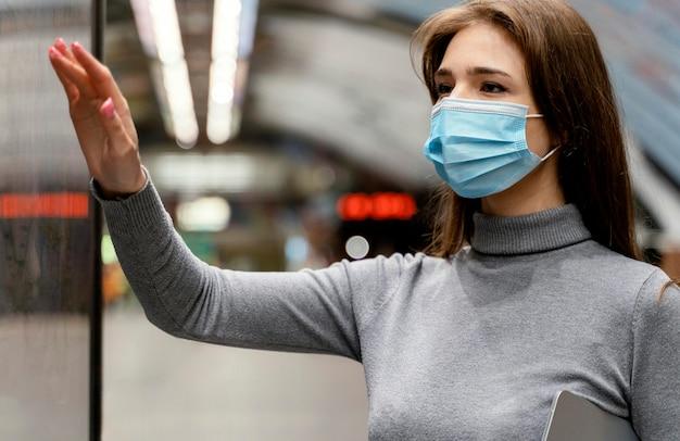 Jonge vrouw te wachten in een metrostation met een tablet Gratis Foto