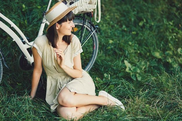 Jonge vrouw tegen aardachtergrond met fiets