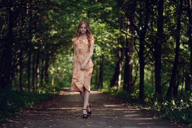 Jonge vrouw, tegen de achtergrond van de zomer groen park, groene bladeren. lopend meisje met mooi krullend haar
