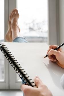 Jonge vrouw tekening thuis in de buurt van het raam