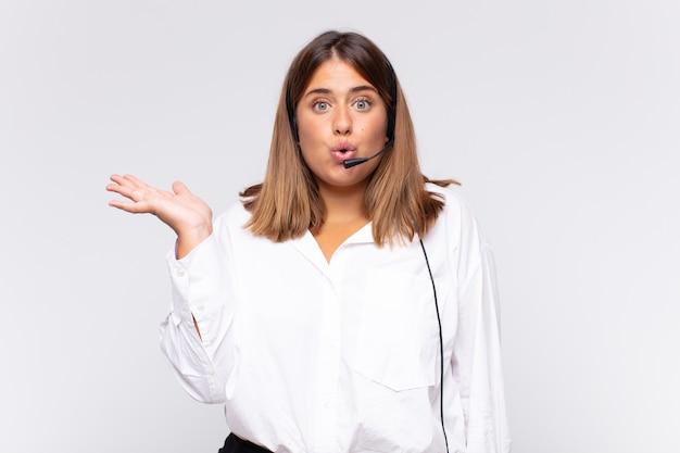 Jonge vrouw telemarketeer die verbaasd en geschokt kijkt, met open mond een voorwerp vasthoudend met een open hand op de zijkant