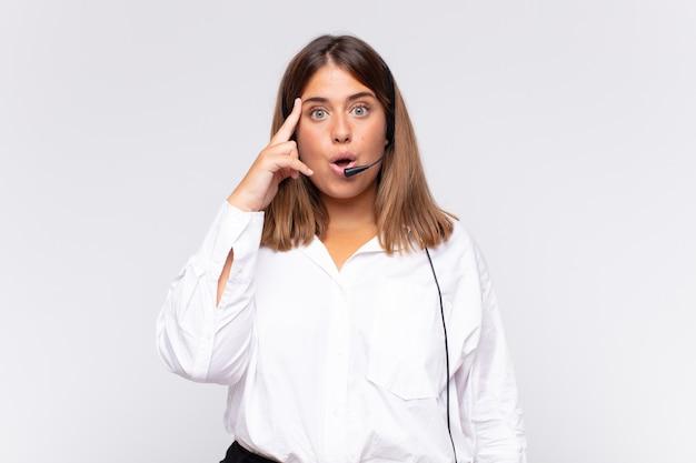 Jonge vrouw telemarketeer die verbaasd, met open mond, geschokt kijkt, een nieuwe gedachte, idee of concept realiseert