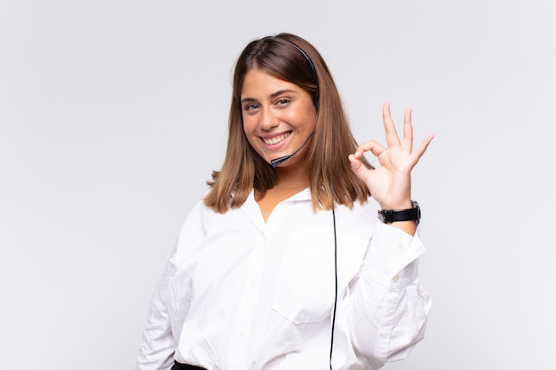 Jonge vrouw telemarketeer die zich gelukkig, ontspannen en tevreden voelt, goedkeuring toont met een goed gebaar, glimlachend