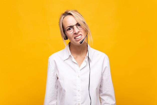Jonge vrouw telemarketeer die zich verbaasd en verward voelt, met een domme, verbijsterde uitdrukking op zoek naar iets onverwachts