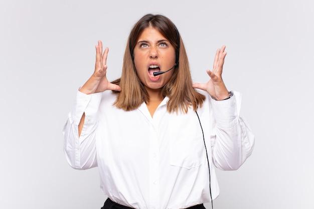 Jonge vrouw telemarketeer schreeuwen met handen in de lucht, woedend, gefrustreerd, gestrest en boos