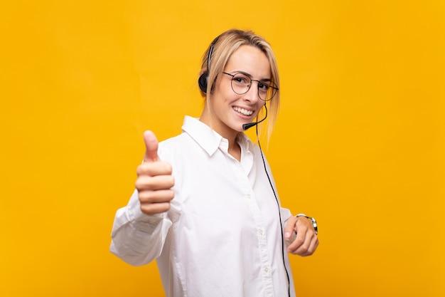 Jonge vrouw telemarketeer voelt zich trots, zorgeloos, zelfverzekerd en gelukkig, positief glimlachend met duimen omhoog