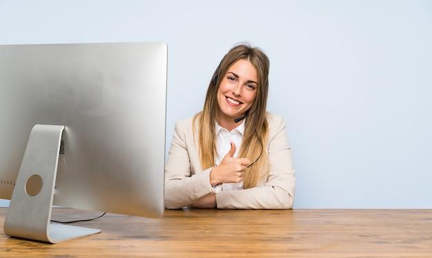 Jonge vrouw telemarketer die duimen op gebaar geeft
