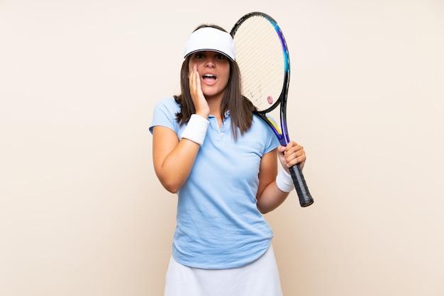 Jonge vrouw tennissen met verrassing en geschokt gelaatsuitdrukking