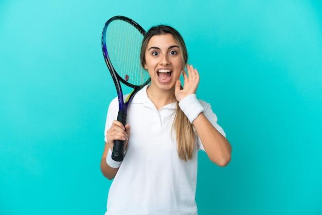 Jonge vrouw tennisser geïsoleerd met verrassing en geschokte gezichtsuitdrukking