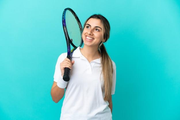 Jonge vrouw tennisser geïsoleerd op blauwe achtergrond denken een idee terwijl opzoeken