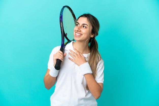 Jonge vrouw tennisser geïsoleerd op blauwe achtergrond terwijl ze glimlacht