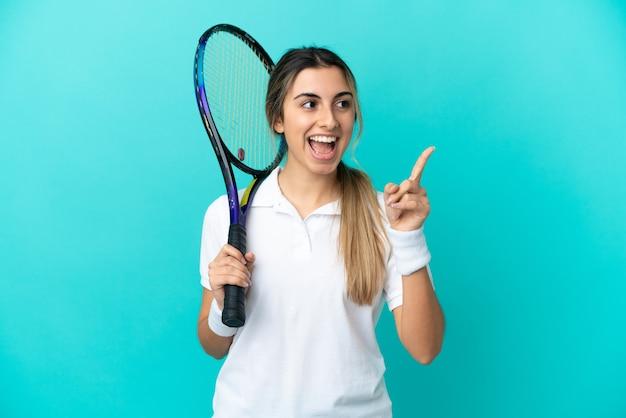Jonge vrouw tennisser geïsoleerd op blauwe achtergrond van plan om de oplossing te realiseren terwijl het opheffen van een vinger Premium Foto