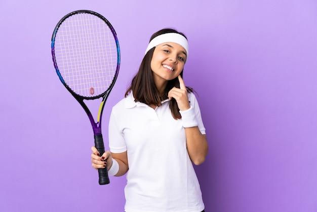 Jonge vrouw tennisser over geïsoleerde muur lachen