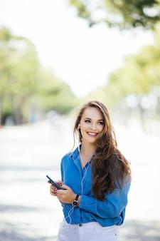 Jonge vrouw texting op de slimme telefoon lopen in de straat in een zonnige dag