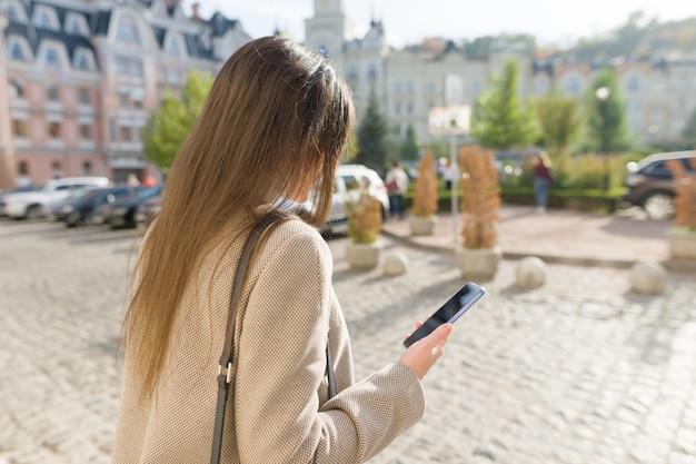 Jonge vrouw texting op de slimme telefoon lopen