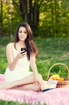 Jonge vrouw texting op weide