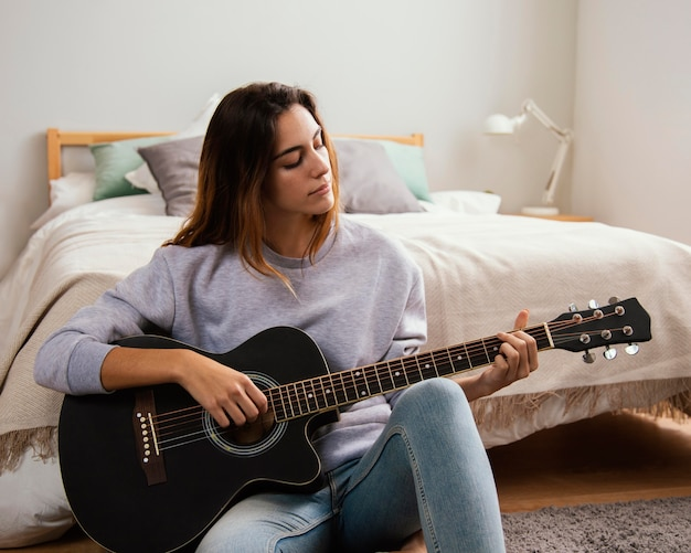 Jonge vrouw thuis gitaarspelen