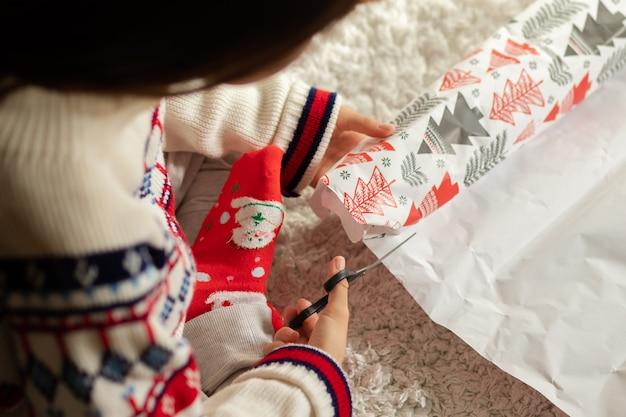 Jonge vrouw thuis inpakken van cadeaus voor kerstmis en nieuwjaar, papier snijden met een schaar
