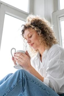 Jonge vrouw thuis koffie drinken in de buurt van het raam