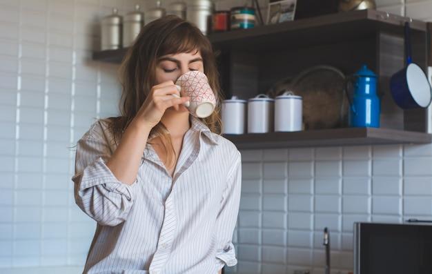Jonge vrouw thuis koffie drinken