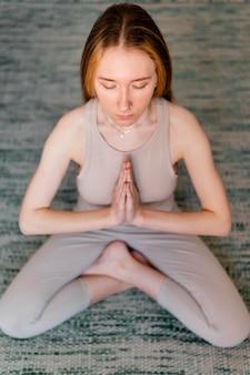 Jonge vrouw thuis mediteren