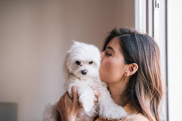 Jonge vrouw thuis met haar leuke maltese hond