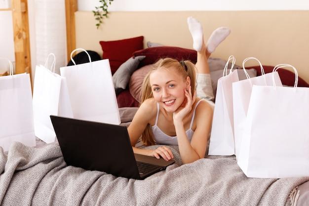Jonge vrouw thuis met laptop en witte papieren zakken