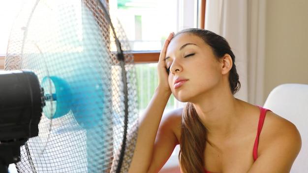 Jonge vrouw thuis met werkende ventilator in hete zomerdag die aan hitte lijdt.