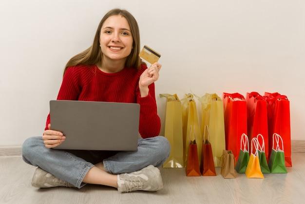 Jonge vrouw thuis online winkelen met behulp van laptop. blij tevreden klant met aankoop