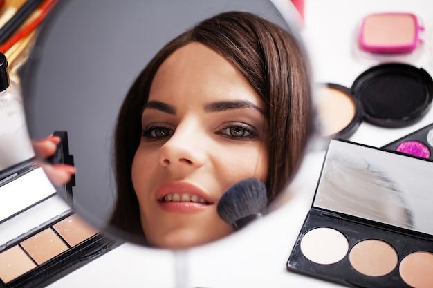 Jonge vrouw thuis past make-up op het gezicht in de slaapkamer voor een spiegel.