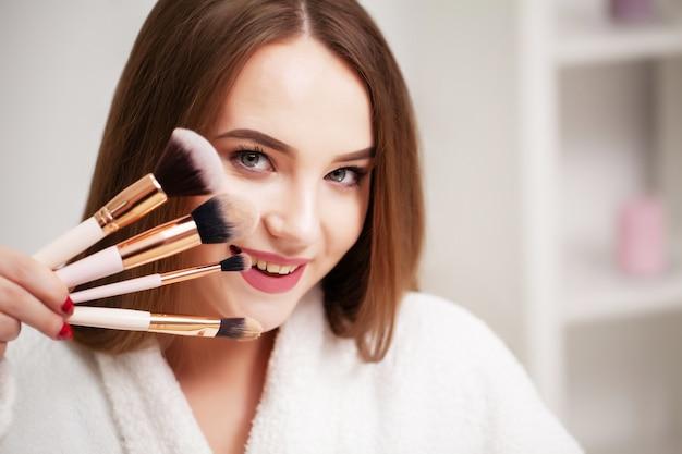 Jonge vrouw thuis past make-up toe op het gezicht in de badkamer voor een spiegel.