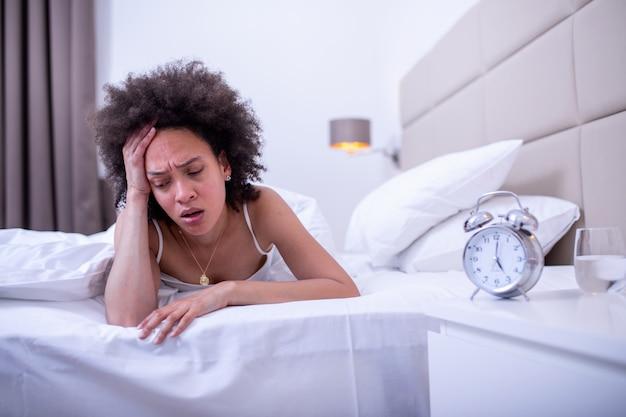 Jonge vrouw thuis slaapkamer liggend in bed laat in de nacht proberen te slapen lijden slapeloosheid slaapstoornis of bang voor nachtmerries op zoek verdrietig bezorgd en gestrest