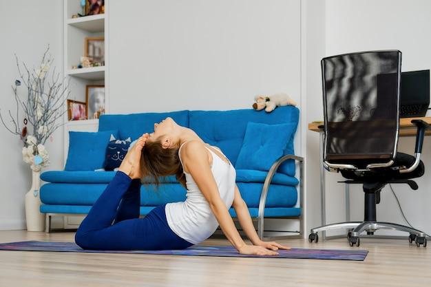 Jonge vrouw thuis yoga beoefenen