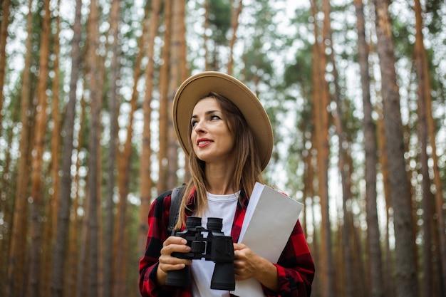 Jonge vrouw toerist in een hoed, rood geruit hemd houdt een kaart en verrekijker in het bos.