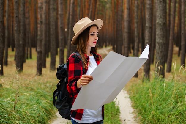 Jonge vrouw toerist in een hoed, rood geruit hemd houdt een kaart van het gebied in het bos.