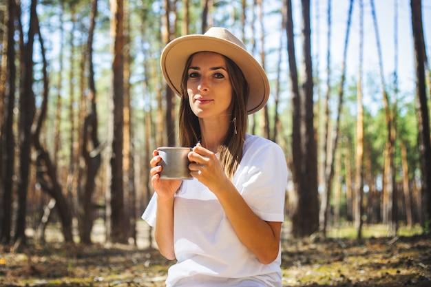 Jonge vrouw toerist in hoed en t-shirt drinkt thee of water tijdens een stop in het bos.