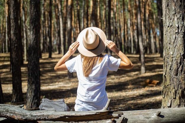 Jonge vrouw toerist in hoed en t-shirt zit op een logboek tijdens een stop in het bos. achteraanzicht.