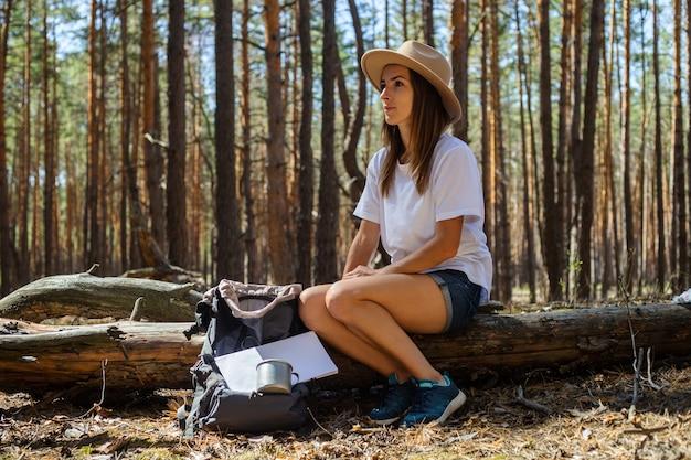 Jonge vrouw toerist in hoed en t-shirt zit op een logboek tijdens een stop in het bos.