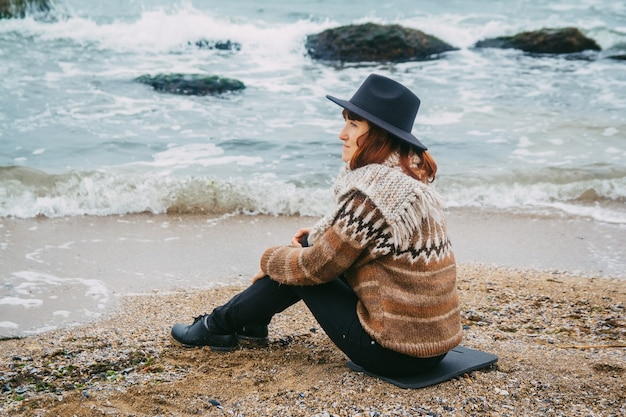 Jonge vrouw toerist in hoed zittend op het strand kijkend naar zee aan de kustlijn aan de horizon
